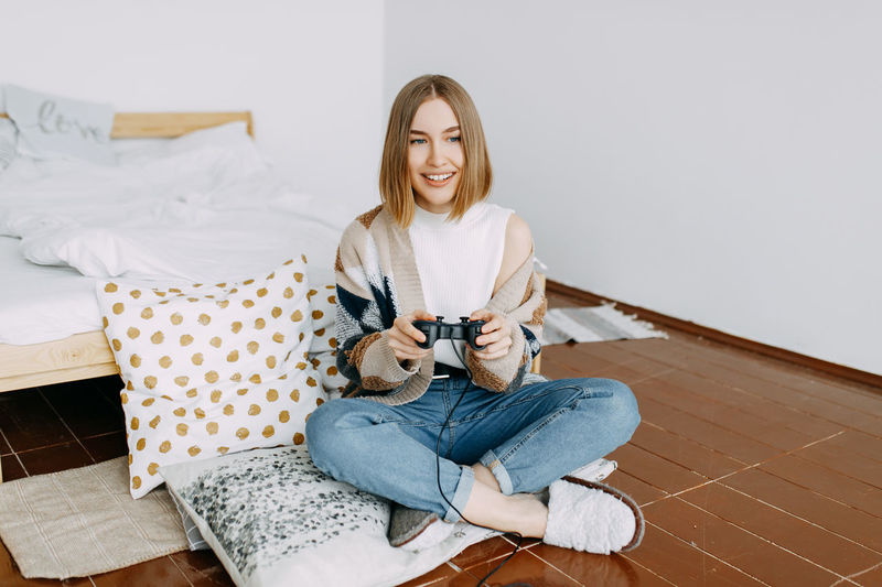 A girl in casual clothes plays on a video console sitting on the floor in the bedroom at home