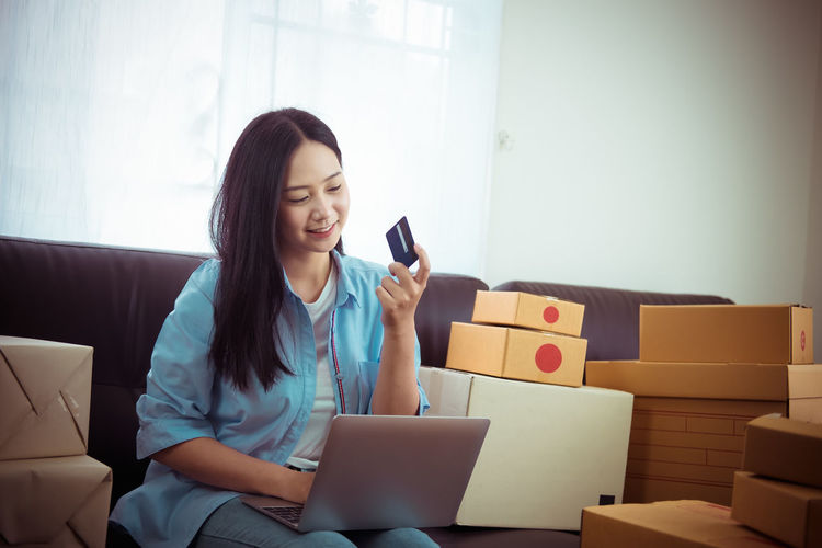 Young woman using phone while sitting in box