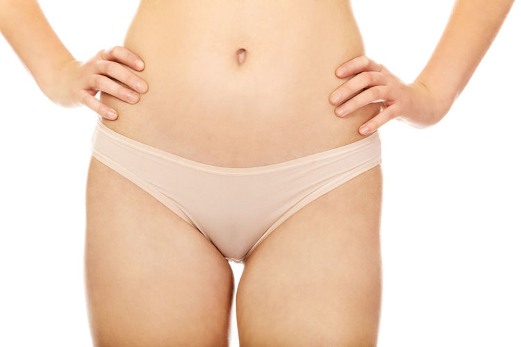 Midsection of young woman with hands on hip standing against white background