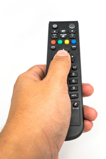 Male hand holding the TV remote control on white background. Close-up Control Electrical Equipment Human Body Part Human Finger Human Hand One Person People Push Button Real People Remote Control Technology White Background
