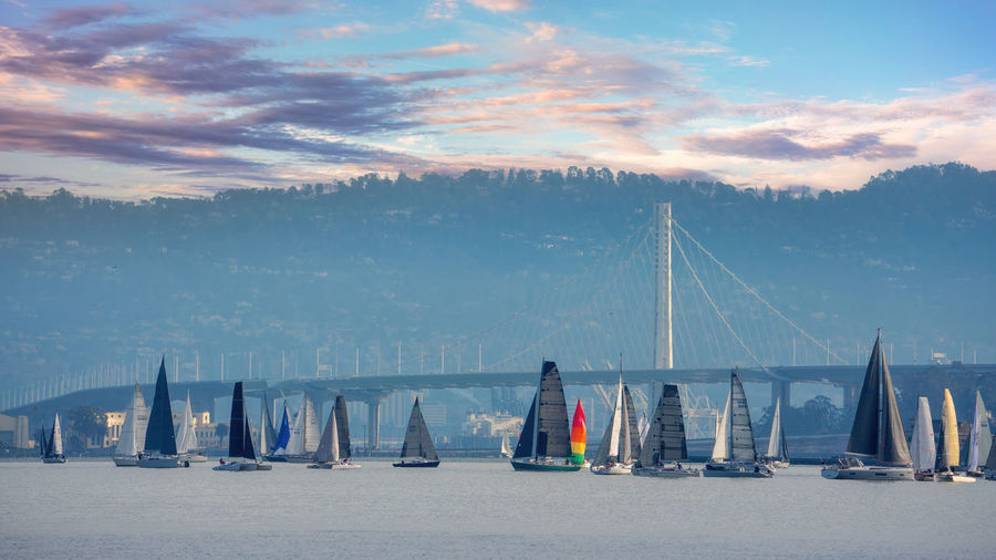Sailboats on bridge against sky