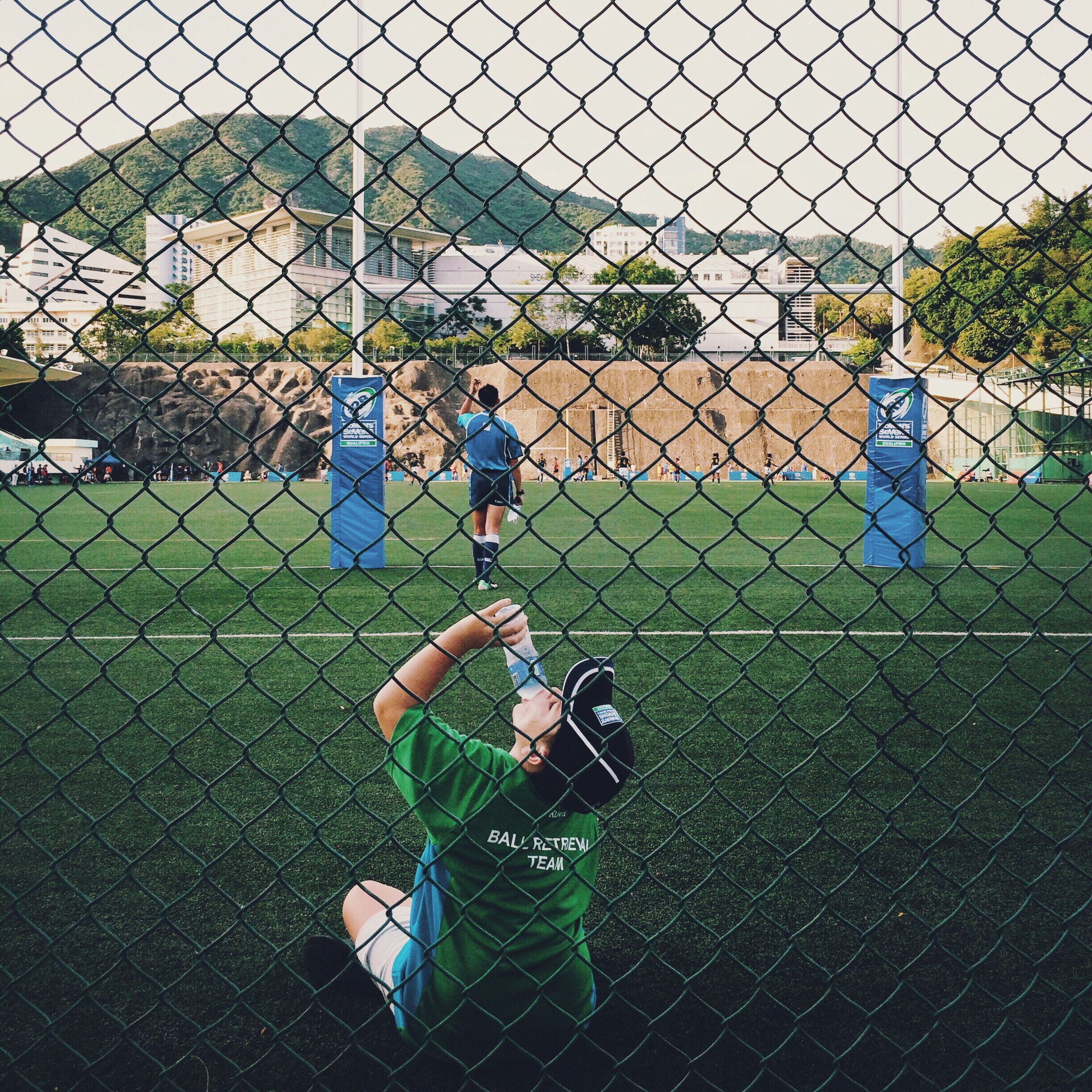 chainlink fence, fence, safety, protection, childhood, security, lifestyles, grass, sport, leisure activity, metal, field, playground, boys, playing, soccer, full length, elementary age, day