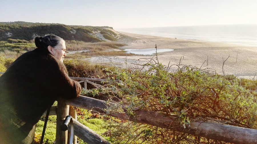 Senior Woman Looking At Sea While Standing By Railing