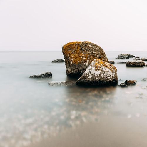 Close-up of rocks on sea against sky