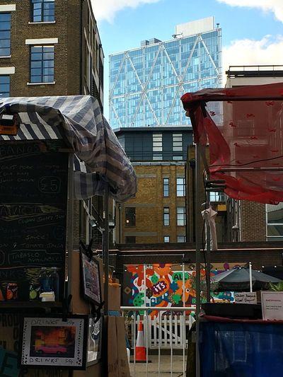 Contrast between Modern Skyscrapers and Rudimental  Food Stall in Bricklane London Uk