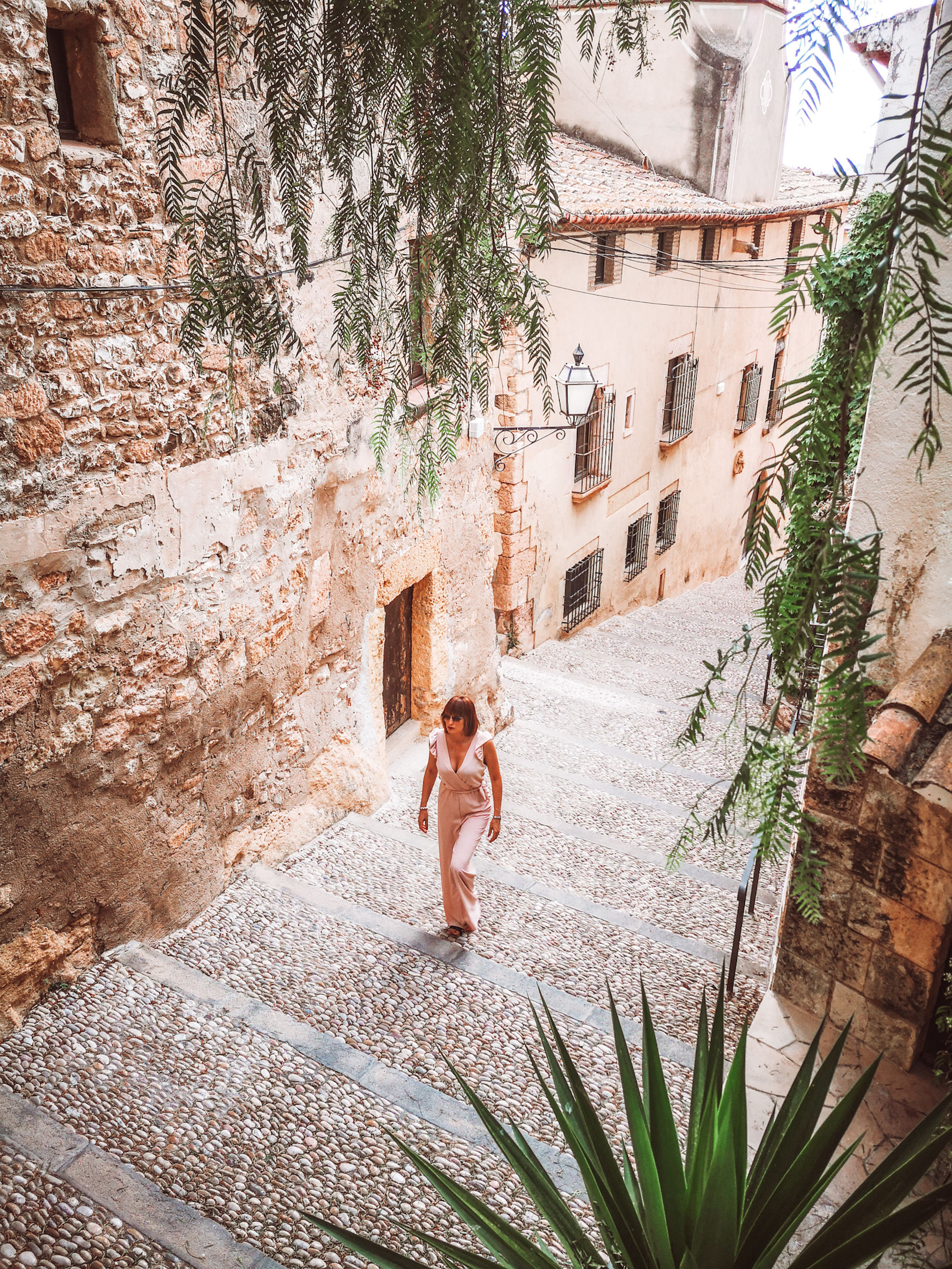 architecture, built structure, building exterior, nature, plant, full length, adult, one person, women, house, day, lifestyles, leisure activity, building, tree, wall, flower, young adult, outdoors, high angle view, sunlight, men, holiday, vacation, courtyard, female, water, trip, standing