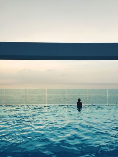Rear View Of Woman In Infinity Pool Against Sea