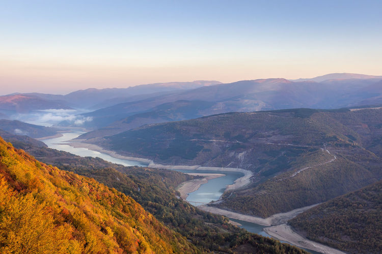 Autumn scene from viewpoint Goat rock viewpoint with soft view of meandering lake Zavoj during misty, moody sunrise Viewpoint Lake Lake View Meandering Narrow Curvy Mountains Morning Sunrise Misty Foggy Hazy  Dawn Autumn colors Forest Golden Hour Sunlit Golden Sky Blue Hour Valley Amazing Beautiful View Landscape Breathtaking View Fall