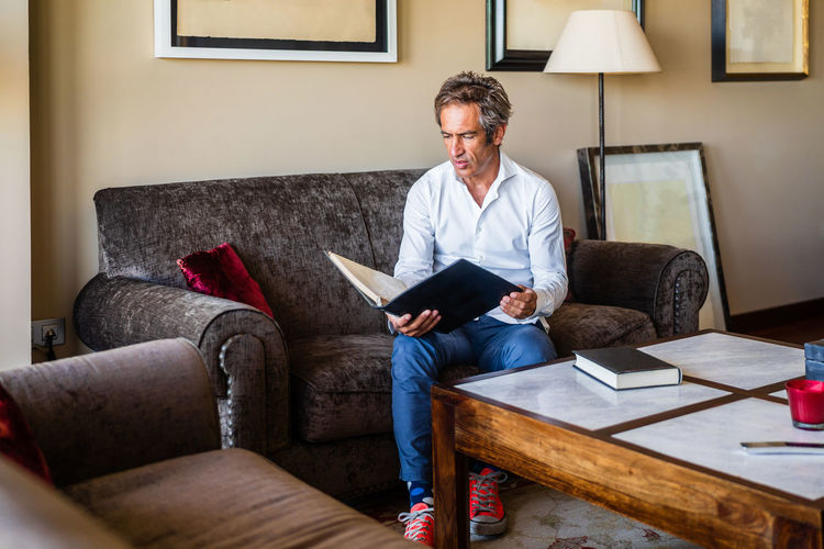 Full length of man sitting on sofa at home