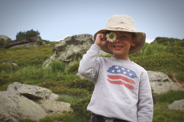 Portrait of smiling boy standing against rock