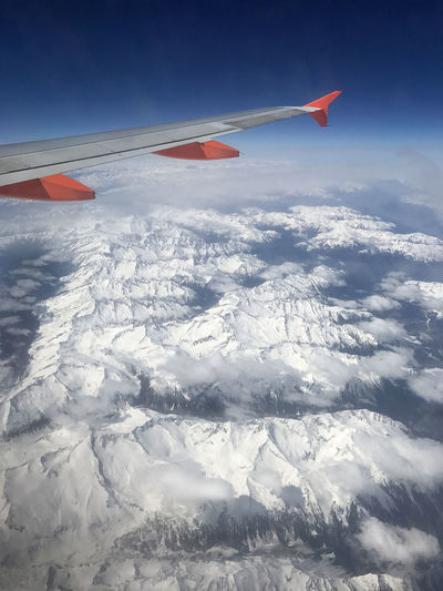 Above The Clouds Aerial View Air Vehicle Aircraft Wing Airplane Airplane Wing Alpine Alps Beauty In Nature Cloud - Sky Day Flying Journey Landscape Mid-air Mountain Nature No People Outdoors Scenics Sky Snow Snow Topped Mountains Transportation Travel