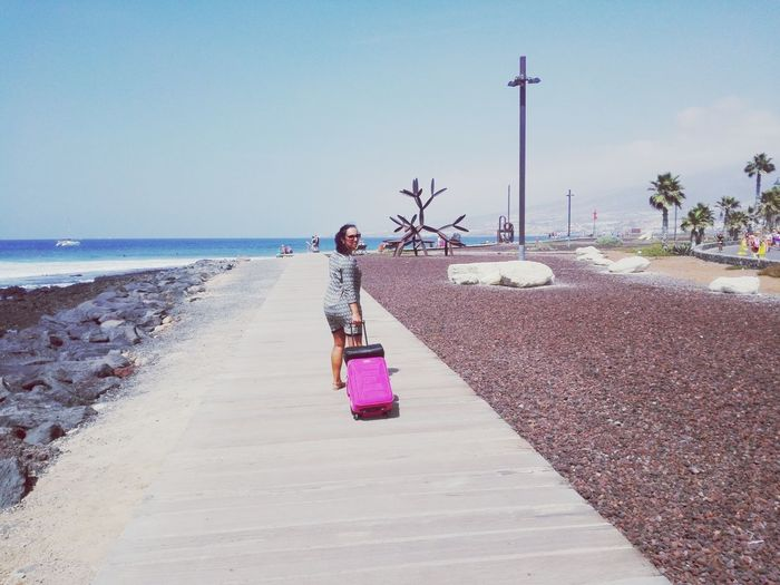 Full length of woman pulling luggage on footpath against sea during sunny day