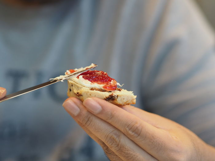 Close-up of person spreading jam on scone