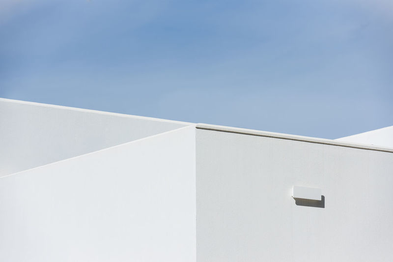 Low angle view of white building against blue sky