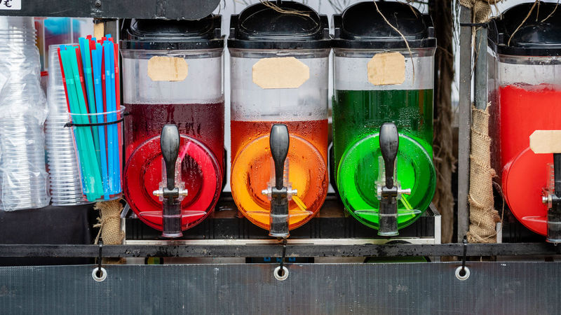 Slush ice drink containers with colorful ice drinks. Colors Food And Drink Frozen Ice Juice Machine Refreshment Syrop Buffet Close-up Cold Cold Temperature Container Crushed Dispenser Drink Equipment Food Fruit In A Row Multi Colored Side By Side Sweet Transparent Variation