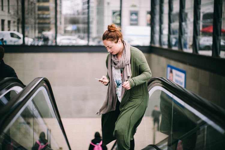 Full length of young woman using mobile phone in bus