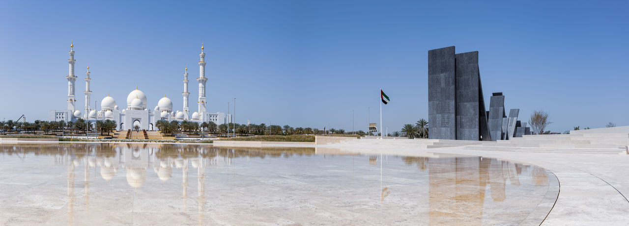 Panoramic view of factory against clear blue sky