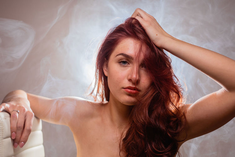 Portrait of beautiful young woman with hand in hair