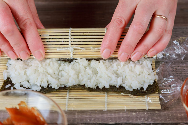 Cropped Hands Preparing Sushi On Table