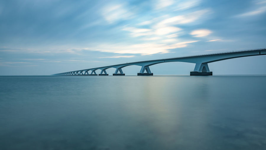 Zeeland Bridge Over Bay Of Water Against Cloudy Sky