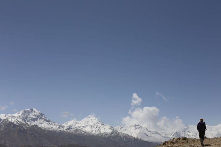 Man standing against snowcapped mountain and sky