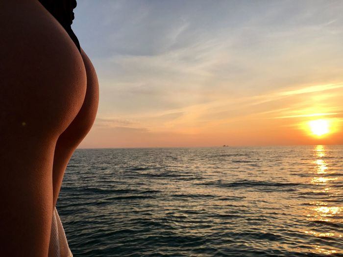 Midsection of sensuous woman in sea against sky during sunset