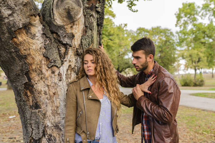 Attractive girl ignoring her boyfriend in the public park Adult Casual Clothing Couple - Relationship Day Hairstyle Leisure Activity Men Nature Outdoors Plant Standing Togetherness Tree Tree Trunk Trunk Two People Young Adult Young Couple Young Men Young Women