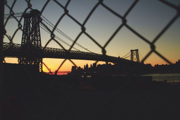 Low angle view of silhouette williamsburg bridge over east river at sunset