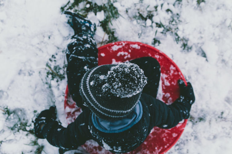 Ice embedded into young boys stocking cap beanie hat as he slides down hill during the winter snow