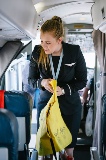 Air stewardess holding life jacket while standing in passenger cabin