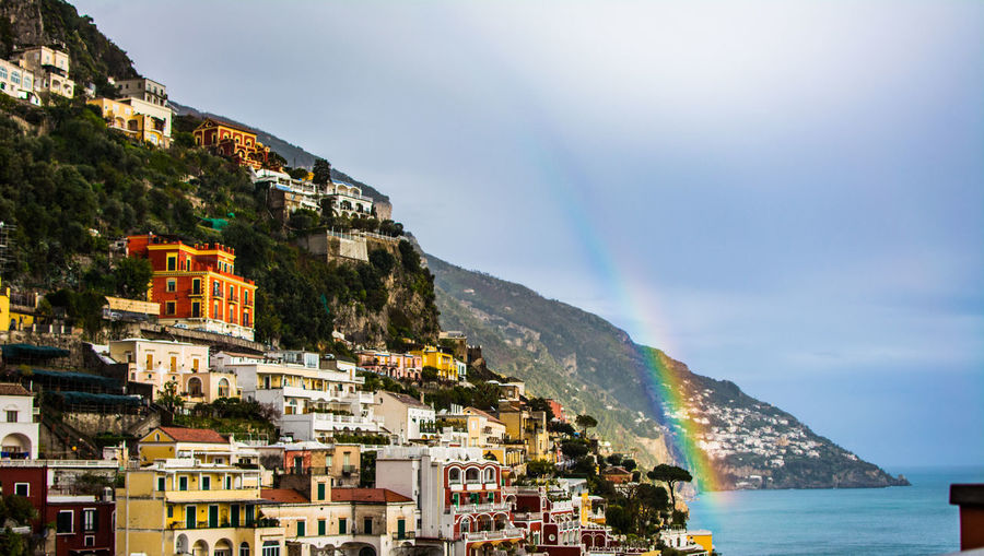 Scenic View Of Rainbow Over Town By Sea Against Sky