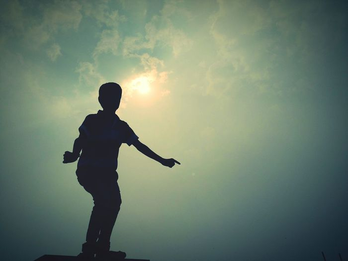 Silhouette boy dancing against sky during sunset
