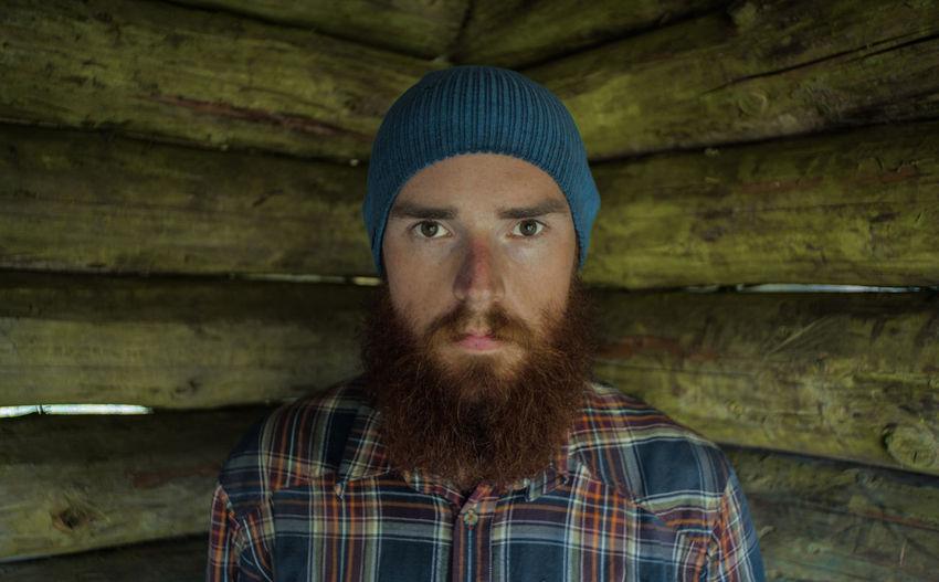 Portrait of bearded man by wooden wall