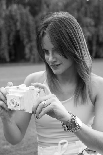Smiling young woman holding toy camera on land