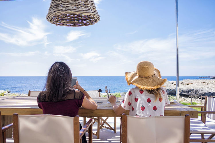 Rear view of two woman sitting in front of the sea while relaxing Water Sea Horizon Over Water Sky Horizon Beach Women Land Real People Chair Beauty In Nature Nature Adult Sitting Rear View Leisure Activity Scenics - Nature Lifestyles Table Outdoors Hairstyle