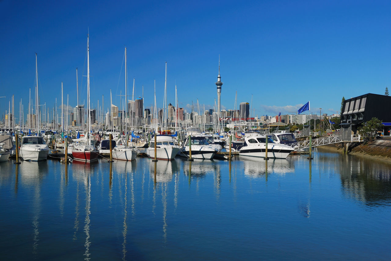 nautical vessel, architecture, building exterior, built structure, moored, transportation, mode of transport, waterfront, reflection, no people, water, travel destinations, outdoors, clear sky, blue, day, sky, mast, harbor, yacht, nature, city
