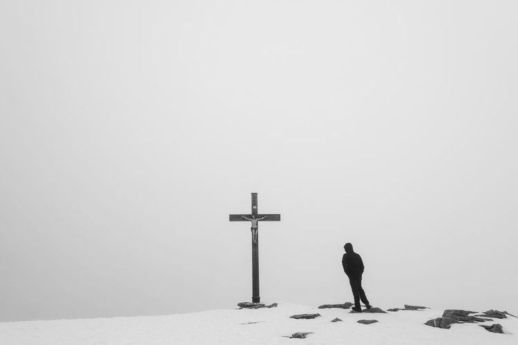 Man standing on snow covered hill by religious cross against sky during winter