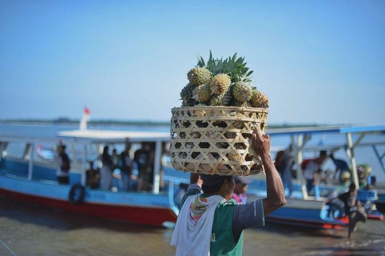 Man carrying pineapples in wicker basket at beach