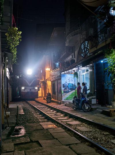Train on railroad tracks in city at night