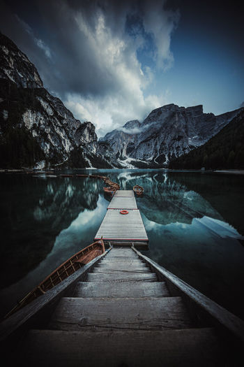 Scenic view of braies lake by snowcapped mountains against sky