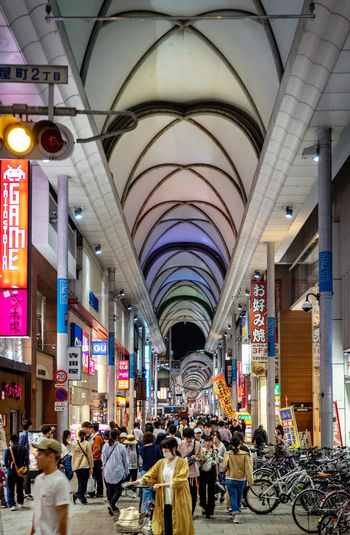 Architecture Group Of People Large Group Of People Real People Built Structure Women Crowd Men Adult Arch Ceiling Lifestyles Shopping Walking Retail  Indoors  Lighting Equipment Illuminated Market Architectural Column Consumerism