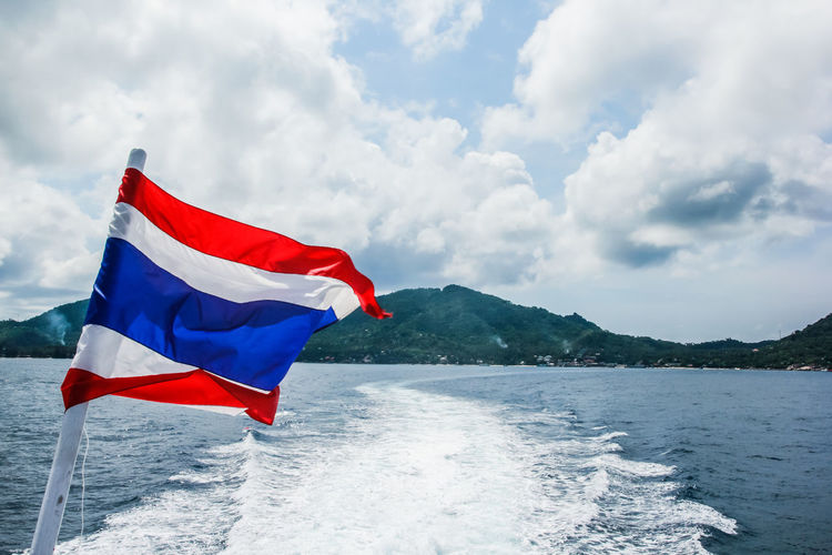 flag of Thailand on a ship in the sea, flag on a ferry with clear sky and deep blue sea background Sky Flag Water Cloud - Sky Patriotism Mountain Red Nature Day No People Wind Environment Motion Sea Scenics - Nature Beauty In Nature Blue Boat Travel Landscape Tourism Transportation ASIA Nature Summer Beach Backgrounds Island Thailand Thai Thailand Flag View National Ship Beautiful Vacations Outdoors Holiday Closeup Flagpole Colorful Coast Clear Sky State City Vessel Flags Horizontal Lines Cruise Transport