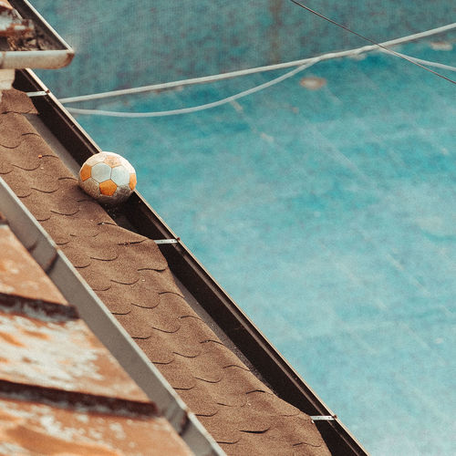 Low angle view of ball hanging on swimming pool against wall