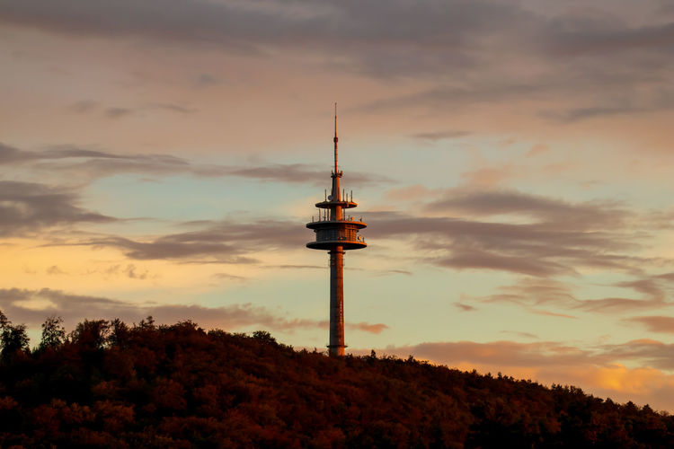 Low angle view of communications tower against sky during sunset