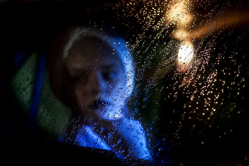 Girl sitting in car seen through wet glass