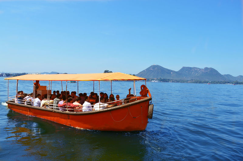 People traveling in boat at lake against sky