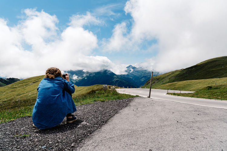 Woman taking photos in the road against mountains Austria Road Taking Photos Trip Adult Alps Beauty In Nature Casual Clothing Cloud - Sky Day Environment Full Length Journey Landscape Mountain Mountain Range Nature Non-urban Scene One Person Outdoors Photographer Real People Rear View Road Scenics - Nature Sky Transportation Traveler Women Summer Road Tripping