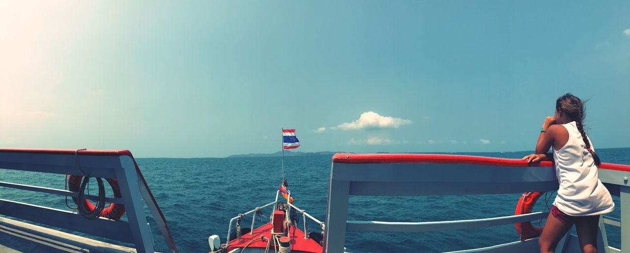 Rear view of woman standing on boat in sea against blue sky