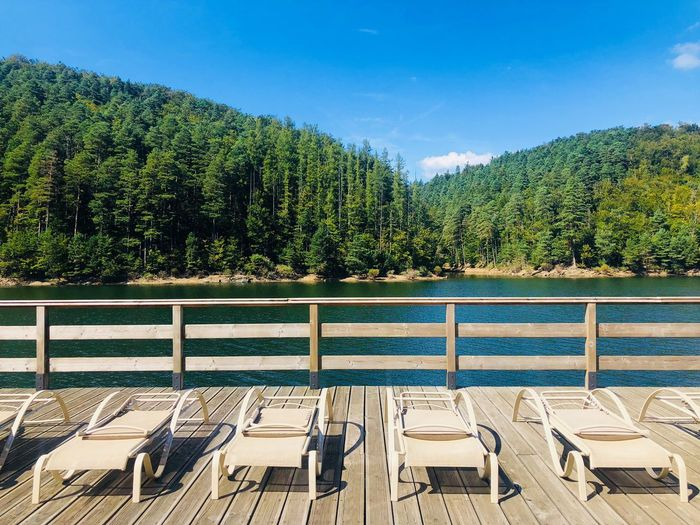 Empty sunbeds on wooden pontoon near the lake on a day with clear blue sky