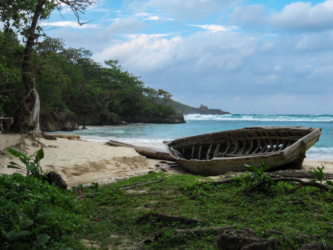 Coastline Grounded Old Boat Tree Weathered Wooden Boat Wreck Abandoned Beach Beauty In Nature Boat Broken Fishing Boat Hole Nature Nautical Vessel No People Outdoors Rotted Rotten Sand Sea Tranquility Tropical Climate Water Breathing Space